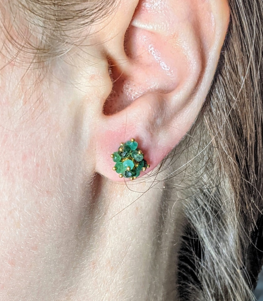 Close-up of a model wearing a pair of emerald beaded stud earrings
