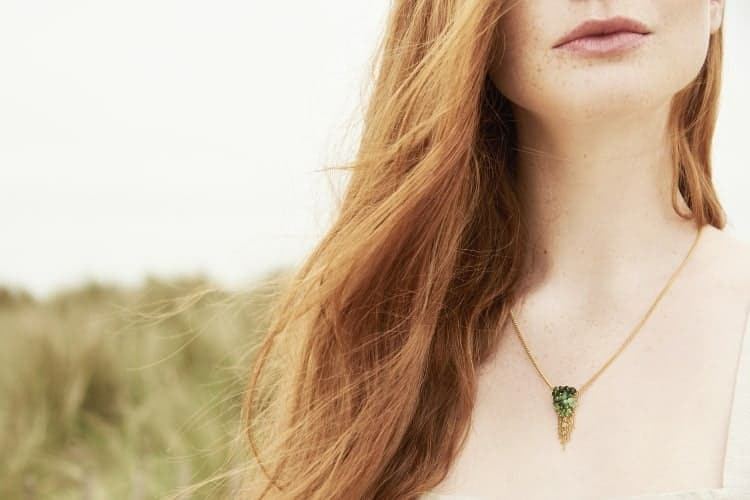Photo of model wearing emerald pendant necklace.