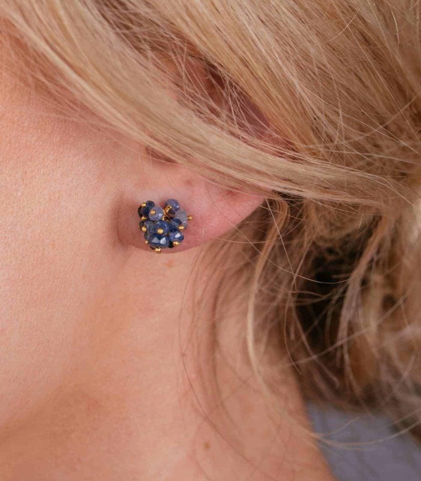 Blue sapphire cluster stud earrings on a model