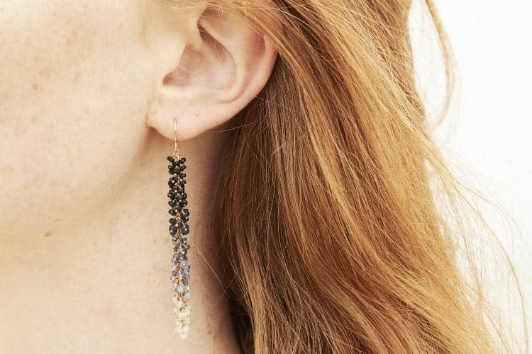 Photo of close up of model wearing sapphire earrings.