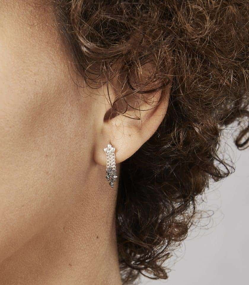 Photo of close up of models ear, wearing diamond and silver stud earring