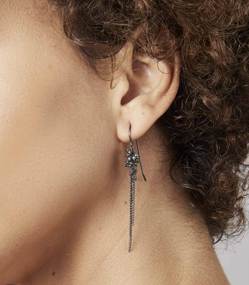 Photo showing close up of Diamond Feather Earrings being worn by model