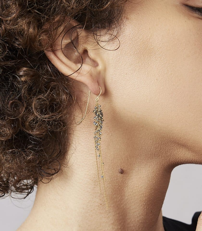 Photo of model wearing sapphire and gold earrings.