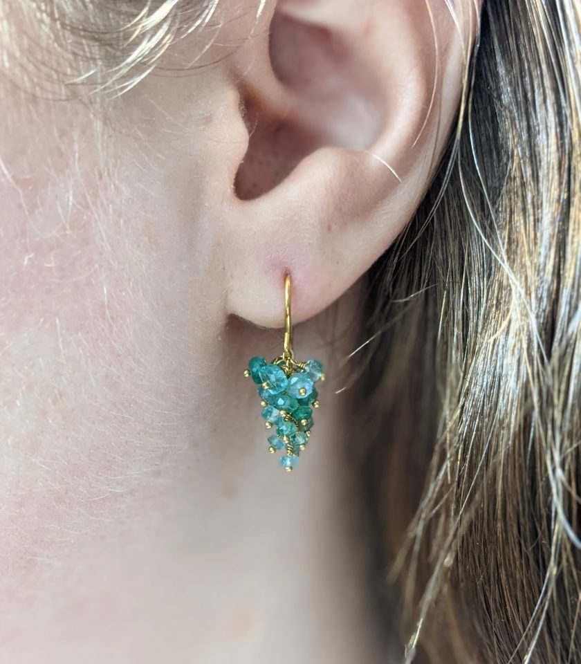 Close-up of a pair of emerald earrings on a mode