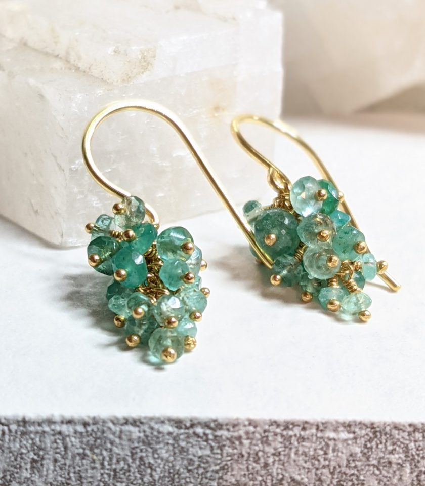 Photo of green emerald drop earrings on a white tile